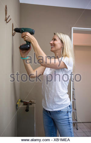 Woman using drill to fix coat hook in apartment - Stock Photo