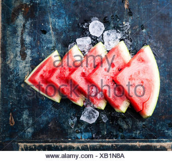 Watermelon slices and ice on blue background - Stock Photo