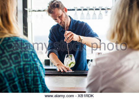 Female customers with bartender making drink at bar counter - Stock Photo
