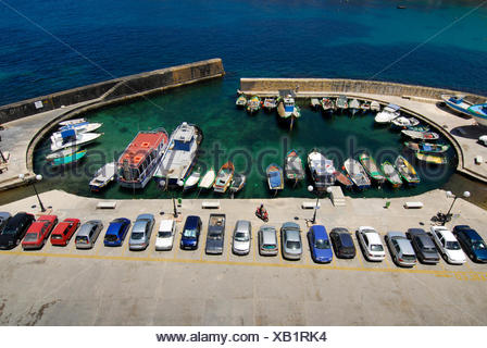 Parked cars and fishing boats in the harbour area, Marsalforn Bay, Marsalforn, Island of Gozo, Malta, Mediterranean Sea, Europe - Stock Photo