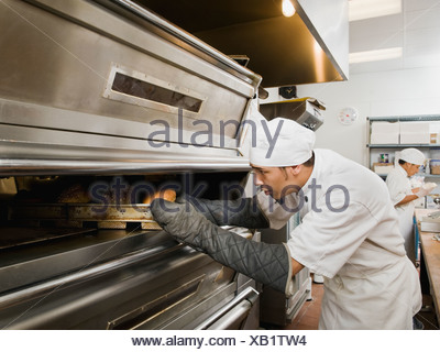 Chef putting bread in oven - Stock Photo