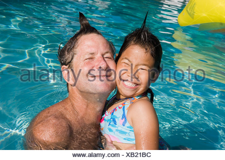 Father and daughter with silly hairdos in pool - Stock Photo