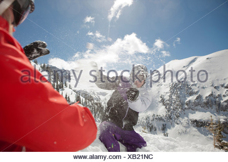 Mid adult man and young woman in skiwear having snowball fight - Stock Photo