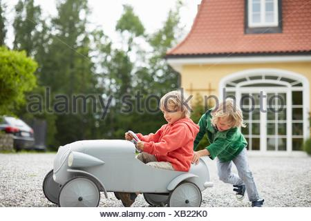 Two boys playing with vintage toy car in front of house - Stock Photo