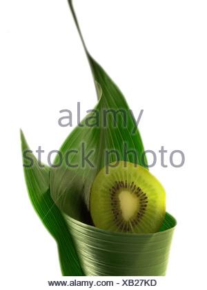 Sliced kiwi wrapped in leaf - Stock Photo
