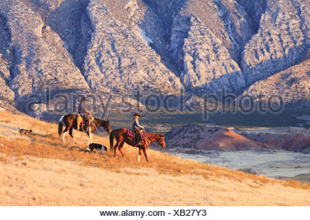 Cowgirl and cowboy riding on Quarter Horses in front of mountain landscape, sunset, USA, Wyoming, Shell, - Stock Photo