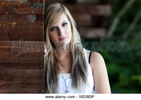 Young woman with long blonde hair standing next to a wooden wall, portrait - Stock Photo