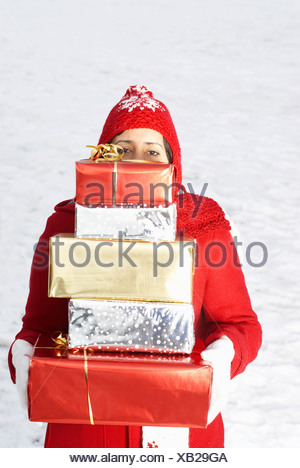 Girl carrying presents in snow - Stock Photo