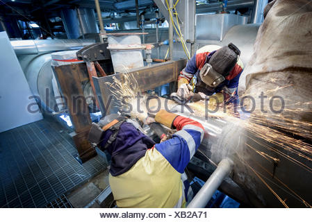 Workers grinding pipe in gas-fired power station - Stock Photo