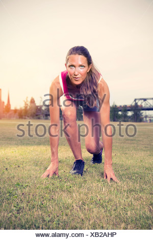 Mature woman exercising in park - Stock Photo