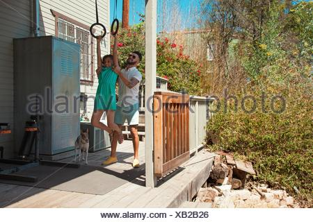 Mid adult man lifting daughter onto exercise rings on patio - Stock Photo