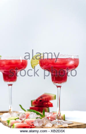 Watermelon margarita in margarita glasses standing on a wooden board photographed from front view. Ice cubes, watermelon slices, lime slices and mint  - Stock Photo