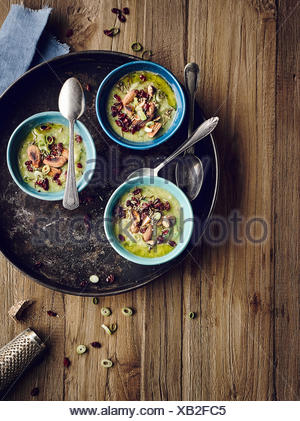 Brussel sprouts soup with salted almonds and barberries - Stock Photo