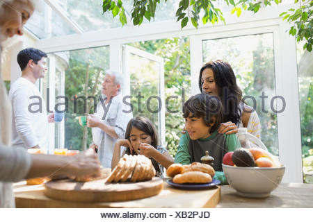 Multi-generation family eating in kitchen - Stock Photo