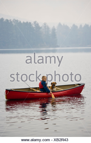 Young boy going fishing with dog in canoe on Source Lake, Algonquin Provincial Park, Ontario, Canada. - Stock Photo