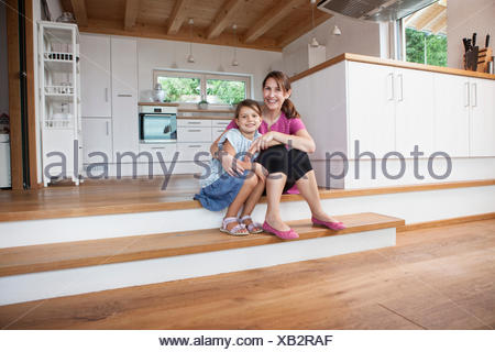 Mother and daughter sitting smiling in kitchen - Stock Photo