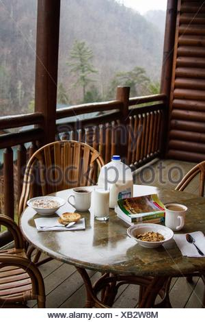 Breakfast table set with milk and cereals on the wooded balcony of a ski resort. The view from the mountains is incredible. - Stock Photo