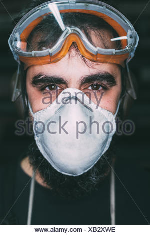 Portrait of male metalworker in dust mask - Stock Photo