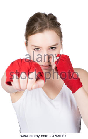 Freigestelltes Foto einer jungen Sportlerin in Box Stellung, die ihre Hände mit einer roten Bandage bandagiert hat. Die Frau schaut verärgert. Gesicht ist scharf. Hand liegt im Unschärfebereich. - Stock Photo