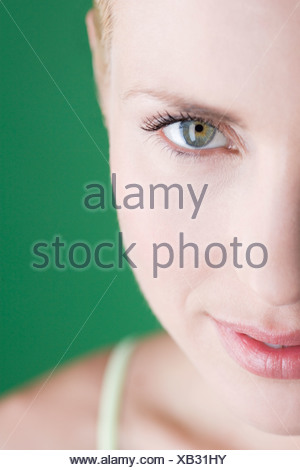 Close-up of a young blonde woman, left hand side of face - Stock Photo