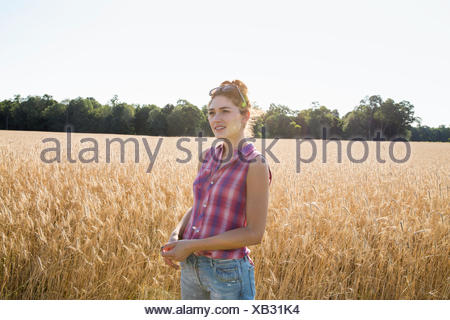 Young woman wearing a checkered shirt standing in a cornfield. - Stock Photo