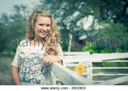 smiling Portrait of young woman leaning on wooden fence - Stock Photo