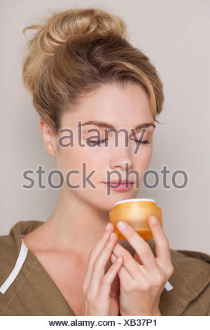Beautiful woman smelling cream - Stock Photo