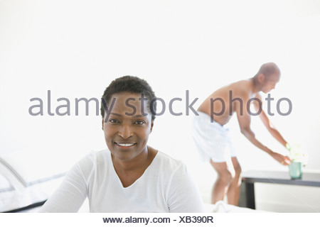 Portrait of woman at home with husband - Stock Photo