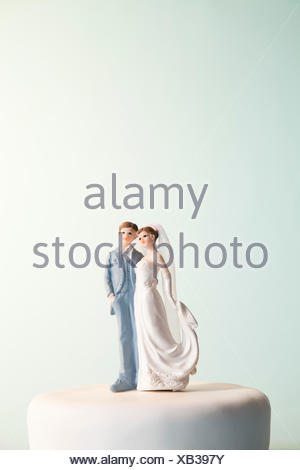 Bride and groom figurines on top of wedding cake - Stock Photo