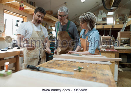 Carpenters discussing wood piece in workshop - Stock Photo