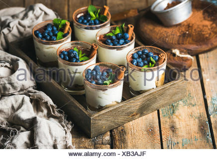 Homemade Tiramisu dessert in glasses with cinnamon, mint and fresh blueberry in wooden tray over rustic wooden background, selec - Stock Photo