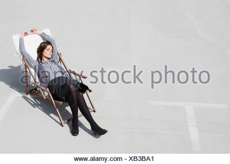 woman relaxing in deck chair - Stock Photo