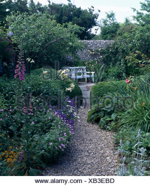 Pink foxgloves and blue perennial geraniums in border beside gravel path to terrace with a white bench in walled garden - Stock Photo