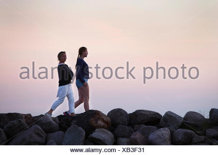 Sweden, Smaland, Woman walking with daughter (14-15) in evening - Stock Photo