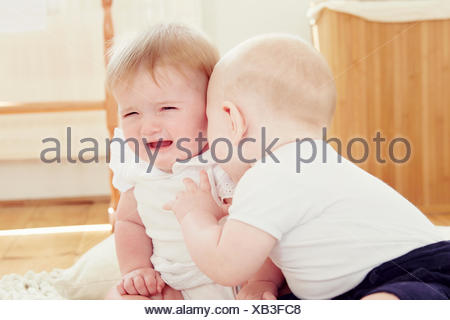 Crying baby girl with baby boy leaning toward her - Stock Photo
