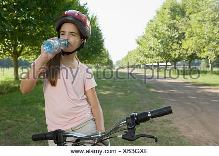 Girl on bike drinking water - Stock Photo