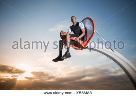 Portrait of a young man sitting in a basketball hoop in a park, Los Angeles, California, USA - Stock Photo