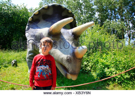Three Horned Dinosaur (Triceratops), little boy standing in front of a Triceratops with its juvenile - Stock Photo