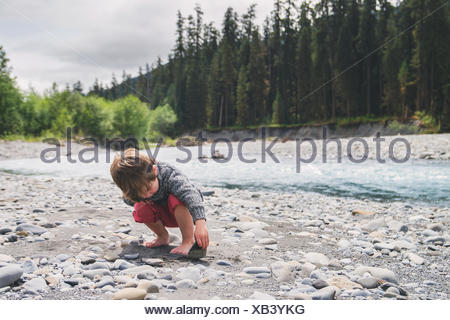 Boy looking under a rock in a river bed - Stock Photo