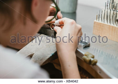 Over shoulder view of female jeweller making ring at workbench - Stock Photo