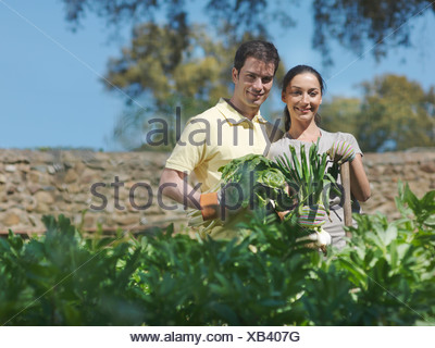 Man and woman with freshly picked vegs - Stock Photo
