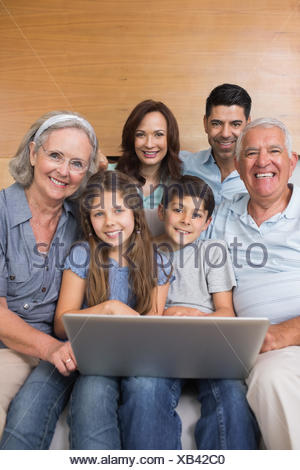 Extended family using laptop on sofa in living room - Stock Photo