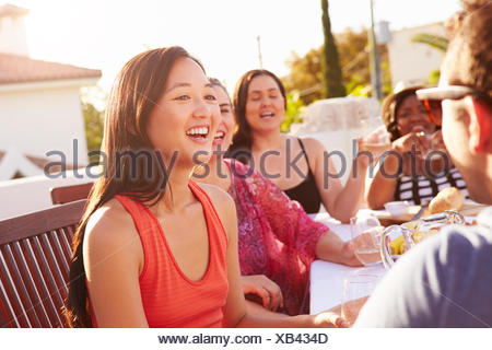 Couple Enjoying Outdoor Summer Meal With Friends - Stock Photo