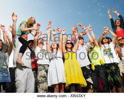Crowd of young people cheering and waving - Stock Photo