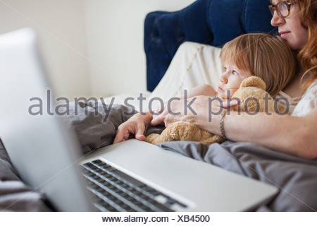 Mother and daughter lying in bed with laptop computer - Stock Photo