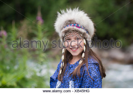 A young Inupiat tween girl in a traditional Eskimo Kuspuk and native headdress, Hatcher Pass, Palmer, Southcentral, Summer - Stock Photo