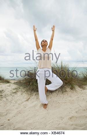 Mature woman in tree pose on beach, portrait - Stock Photo