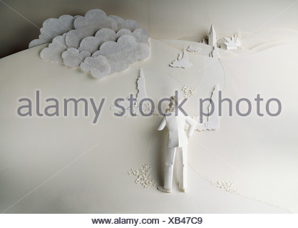 Paper artwork; 3 dimensional paper man standing with hand on hip, other hand on chin, puzzled stance - Stock Photo