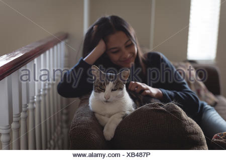 Teenage girl sitting with cat on sofa in living room - Stock Photo