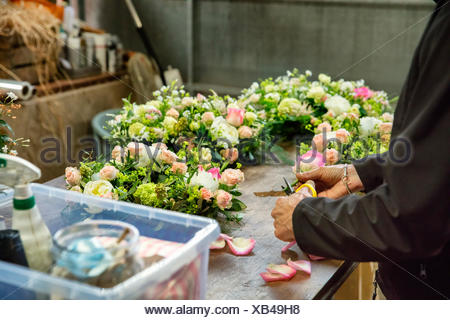 Commercial florist. A woman working on  a floral decoration  at a workbench. - Stock Photo